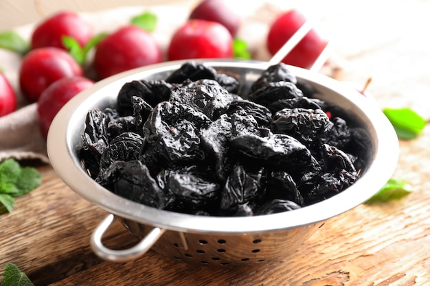Collander with tasty dried plums on table