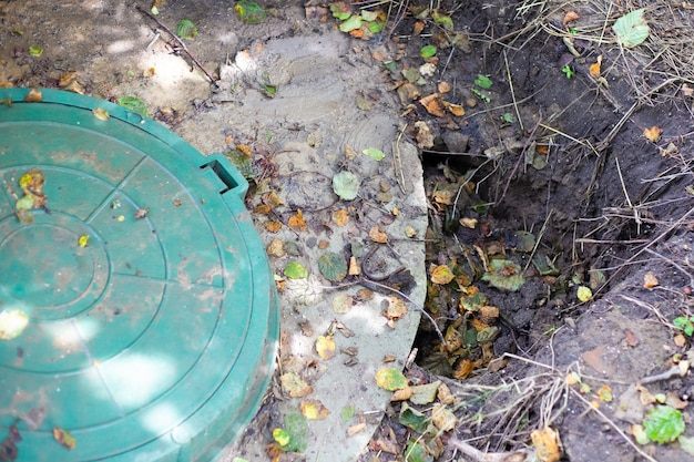 Collapsed soil near the concrete rings of an underground well. installed septic tank, poor soil compaction.