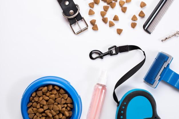 Чаша для ошейника с расческами для деликатесов и щеток для собак, изолированные на белом фоне