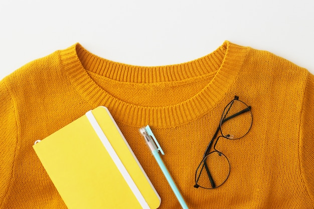 A collar of a bright yellow sweater with a notebook, pen and glasses