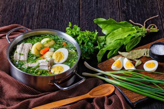 Классический щавелевый суп из свежего щавеля, зеленого лука со свиными ребрышками, молодого картофеля, моркови и вареных яиц, подается в кастрюле на деревянном столе с ингредиентами, крупным планом