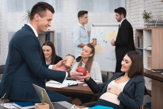 Colleague giving food to pregnant worker in office