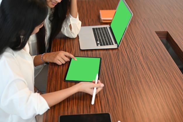 Коллега женщин, работающих с цифровым планшетом и портативным компьютером