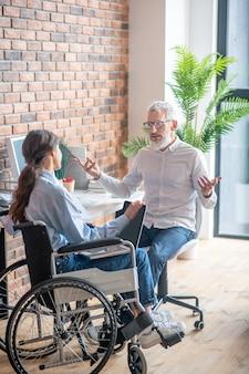 Коллеги по работе. девушка в инвалидной коляске разговаривает со своим коллегой-мужчиной и выглядит вовлеченной