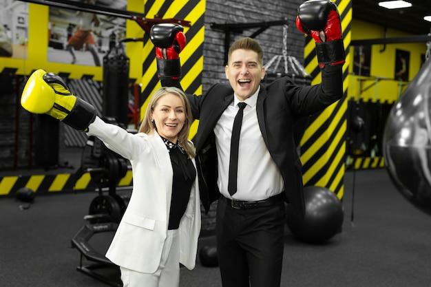 Коллеги, мужчина и женщина в деловых костюмах и боксерских перчатках на ринге поднимают руки вверх, веселятся и смеются.