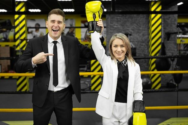 Коллеги, мужчина и женщина в деловых костюмах и боксерских перчатках на ринге.