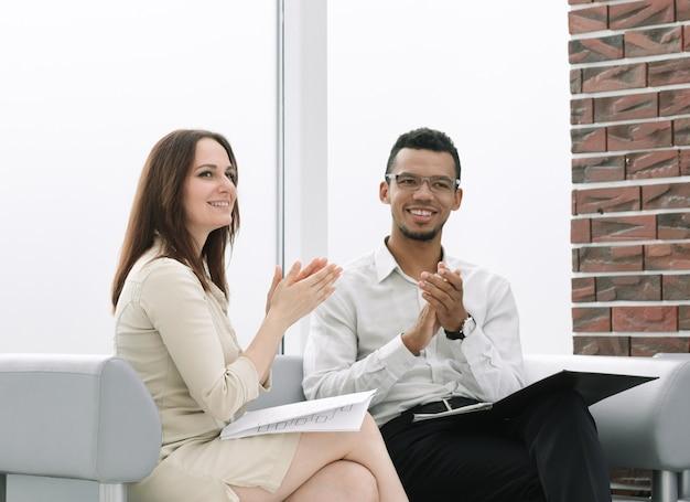 同僚は、オフィスのロビーに座っているビジネスマンを称賛します。