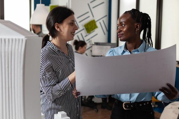 設計図の計画をチェックする同僚の建築家女性