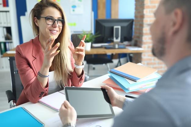 Коллеги сидят за столом в офисе, разговаривают и улыбаются. обсуждение концепции финансирования проекта