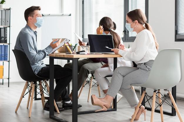 Коллеги по работе во время пандемии в офисе в масках
