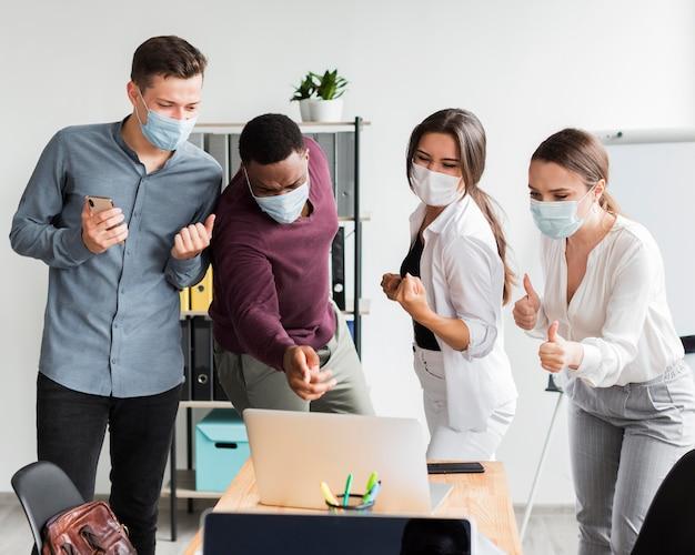 Коллеги на работе в офисе во время пандемии в масках и смотрят на ноутбук