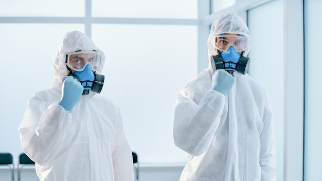 Colleagues in biohazard suits standing in the lab