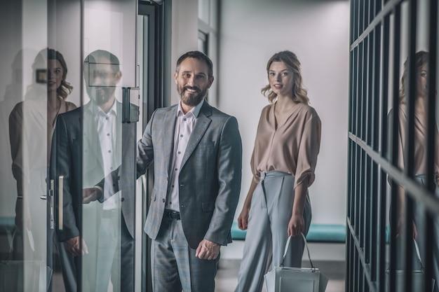 同僚、ビジネス。ビジネス大人の笑顔のひげを生やした灰色のスーツでオフィスのドアを開くと若いブロンドの女性のハンドバッグ