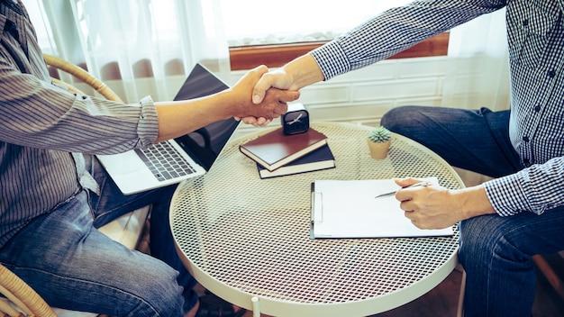 同僚、ビジネスマンが喫茶店に座って握手しながらお互いに仕事について話し合う。