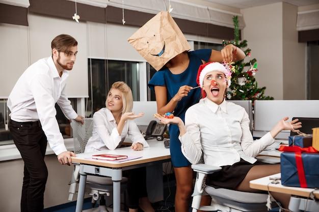 笑顔のシャンパンを飲んでオフィスでクリスマスパーティーを祝っている同僚。