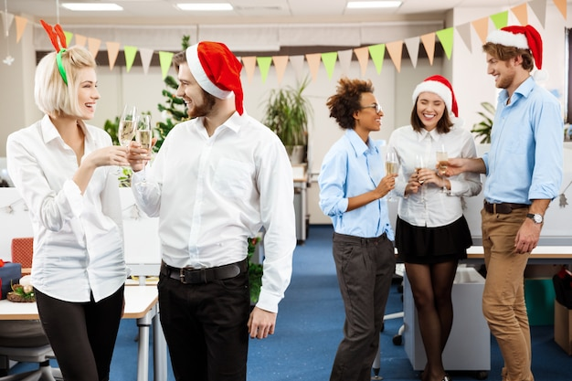 샴페인 웃 고 마시는 사무실에서 크리스마스 파티를 축 하하는 동료.