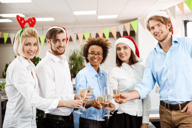 Коллеги, празднование рождества в офисе, пили шампанское улыбается.