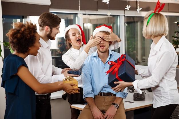Коллеги, празднование рождества в офисе, улыбаясь, давая подарки.