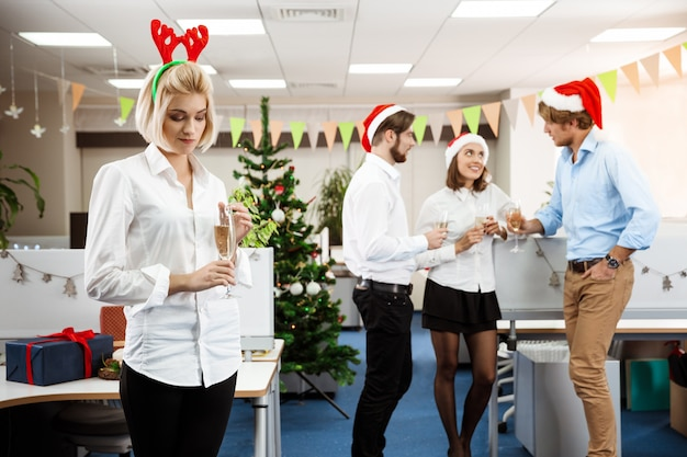 Colleagues celebrating christmas party in office drinking champagne smiling.