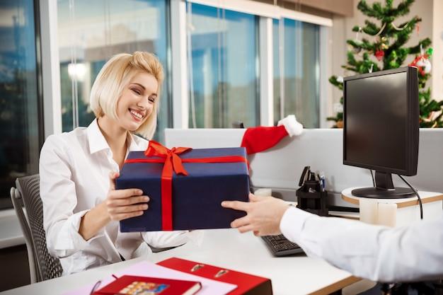 Colleghi che celebrano la festa di natale in ufficio sorridendo dando regali.