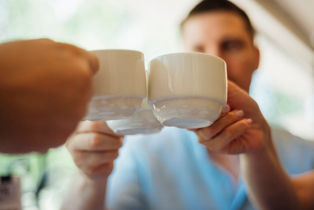 Colleagues clanging cups with hot drinks together