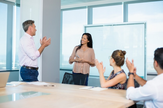 Colleagues clapping for businesswoman in conference room