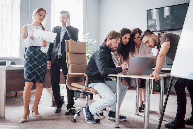 同僚は近代的なオフィスで仕事の質問と通信します
