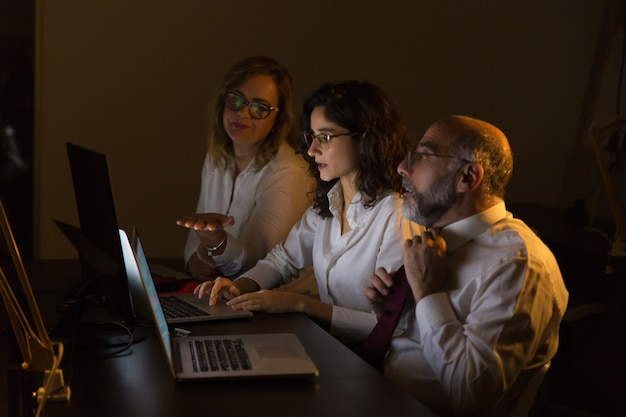 Colleagues discussing work in dark office