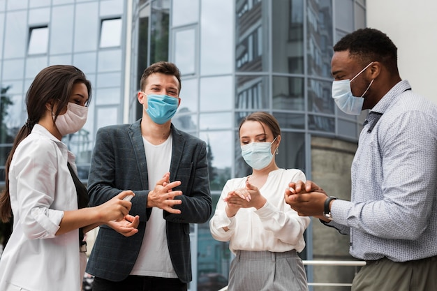 Colleagues disinfecting hands outdoors during pandemic while wearing masks