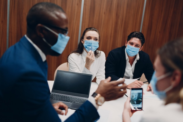 Colleagues diverse team wearing face mask office meeting business people men and women group confere...