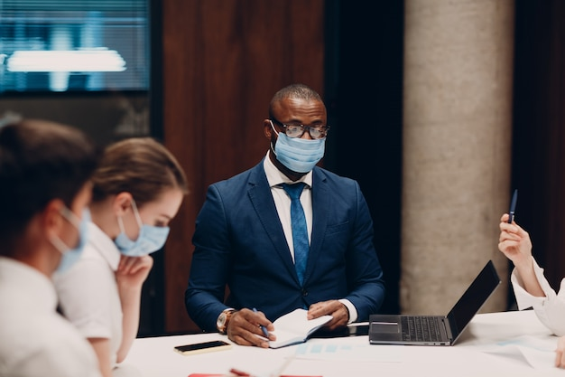 Colleagues diverse team wearing face mask office meeting businessmen and women group conference disc...