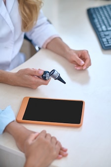 Colleagues, doctors. hands of doctor otolaryngologist in white coat sitting at table with tablet communicating with patient, no face