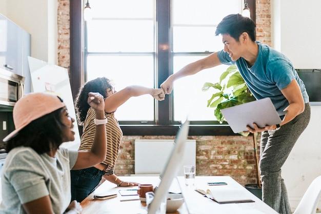 Коллеги бьют кулаком в офисе