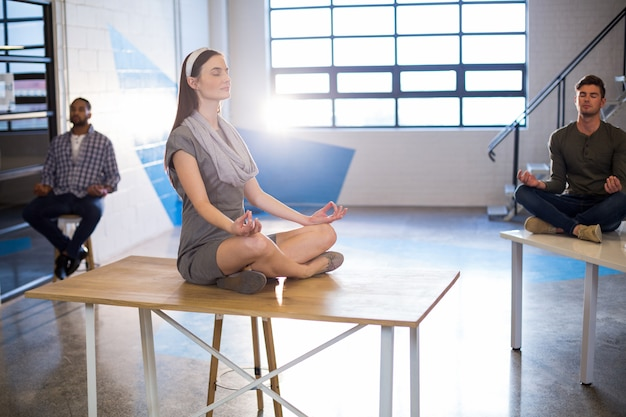Colleagues doing yoga in office