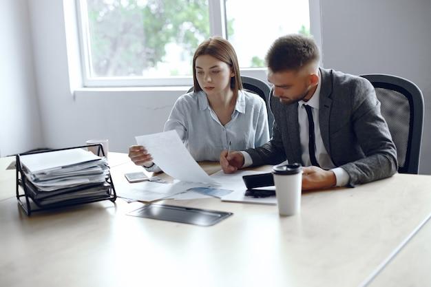 I colleghi bevono caffè partner d'affari in una riunione d'affari uomo e donna seduti al tavolo