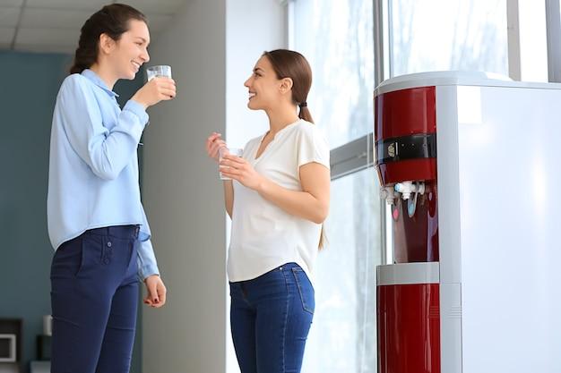 Коллеги пьют воду из кулера во время перерыва в офисе