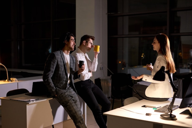 Colleagues in formal outfit stand having conversation, drinking coffee, taking a break at late night in boardroom, smiling, discussing, sharing ideas, explaining plans