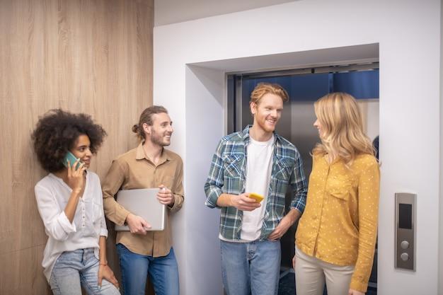Коллеги. группа сотрудников, стоящих возле лифта и разговаривающих