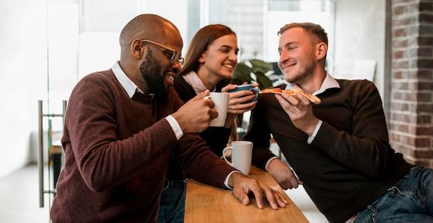 コーヒーを飲みながら会議をしている同僚