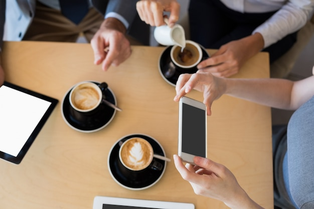 Colleagues having a cup of coffee while using mobile phone and digital tablet