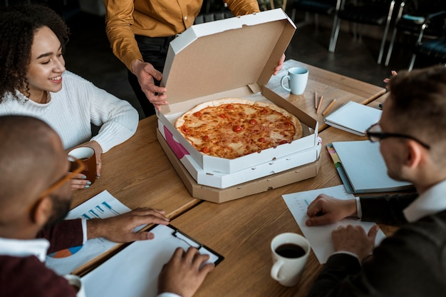 Colleagues having pizza during an office meeting break