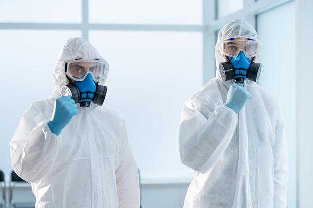 Коллеги в защитных костюмах стоят в лаборатории. концепция охраны здоровья.