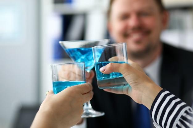 Коллеги в офисе празднуют значительное событие с синей алкогольной жидкостью в очках