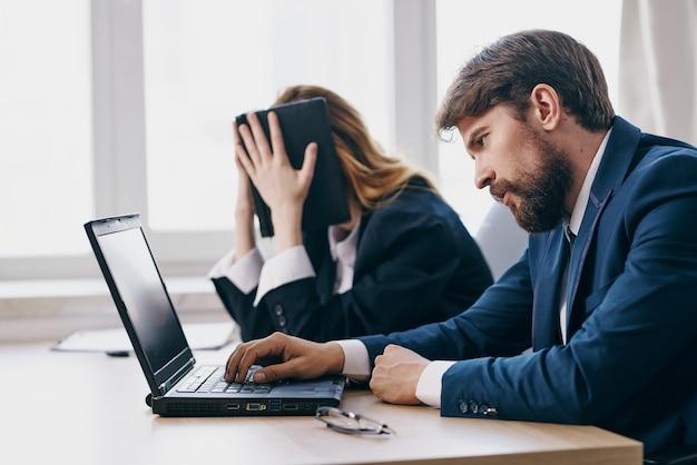 Коллеги в офисе перед чиновниками карьеры ноутбука