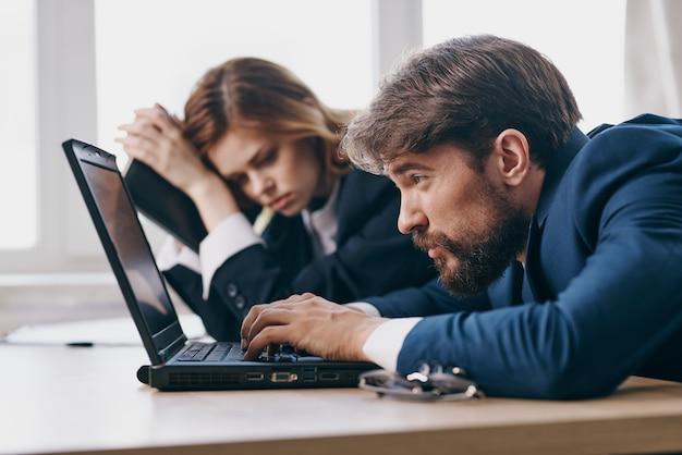 Коллеги в офисе перед ноутбуком работают профессионалы карьеры