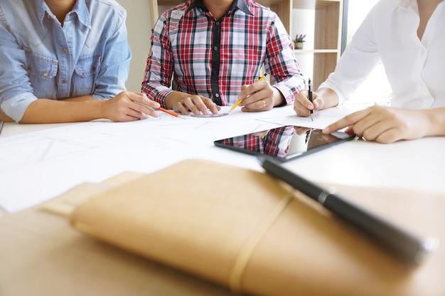 Colleagues interior designer corporate achievement planning design on blueprint teamwork concept with compasses