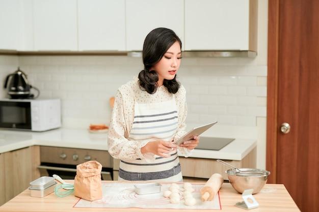 Коллеги замешивают тесто скалкой на кухне пекарни