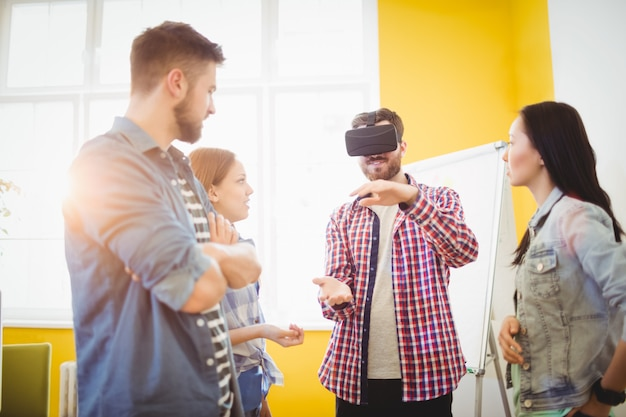 Colleagues looking at businessman wearing virtual reality headset
