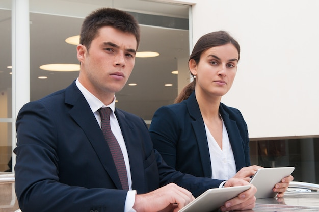 Colleagues looking at camera and holding tablets at desk