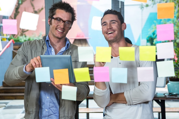 Colleagues looking at sticky notes and tablet